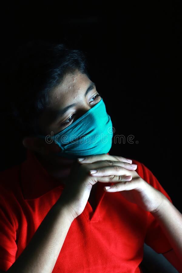 Free Dramatic Portrait Of A Boy Wearing Medical Face Mask Looking Out Deep In Thought. Royalty Free Stock Photography - 179702427