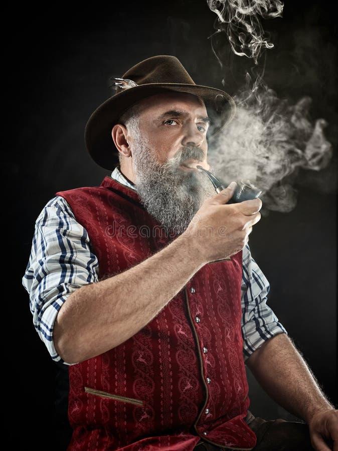 Free Dramatic Portrait Of Senior Smoking Tobacco Pipe Stock Photo - 125597480