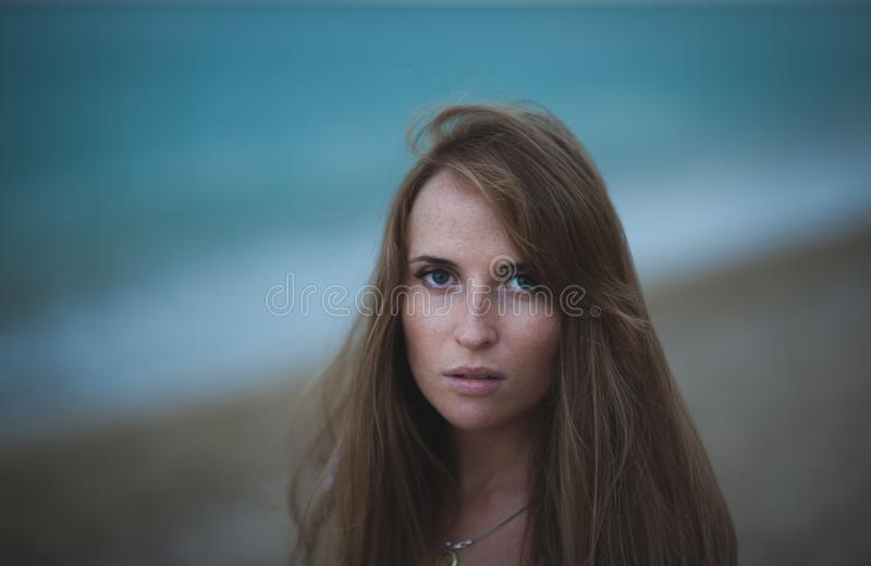 Dramatic portrait of pretty girl with long gorgeous hair near blue sea coast royalty free stock photography