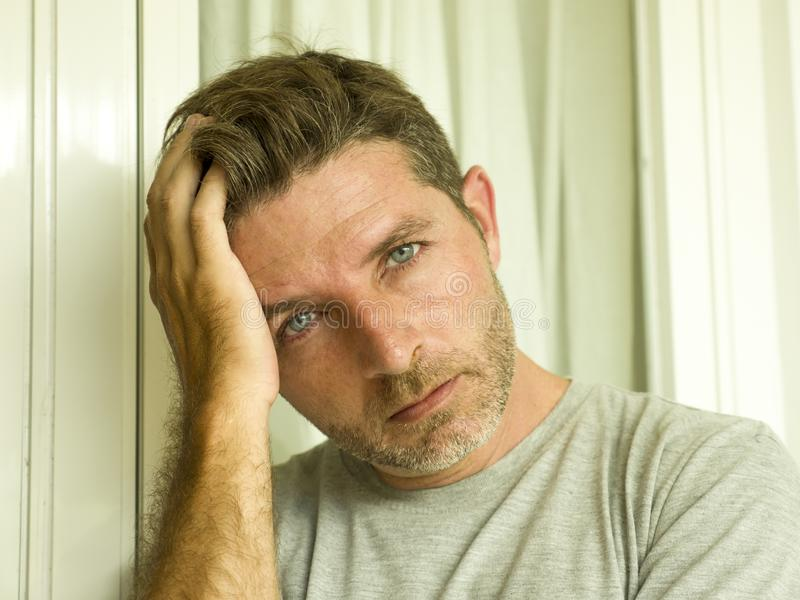Dramatic portrait of sad and depressed 30s or 40s man in pain feeling stressed and broken suffering depression problem and anxiety stock image