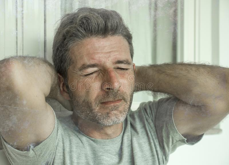 Dramatic portrait of sad and depressed 30s or 40s man in pain feeling stressed and broken suffering depression problem and anxiety stock photography