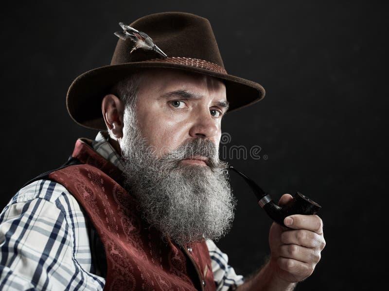 Dramatic portrait of senior smoking tobacco pipe. Dramatic portrait of gray bearded senior man in hat smoking tobacco pipe. view of Austrian, Tyrolean, Bavarian stock images