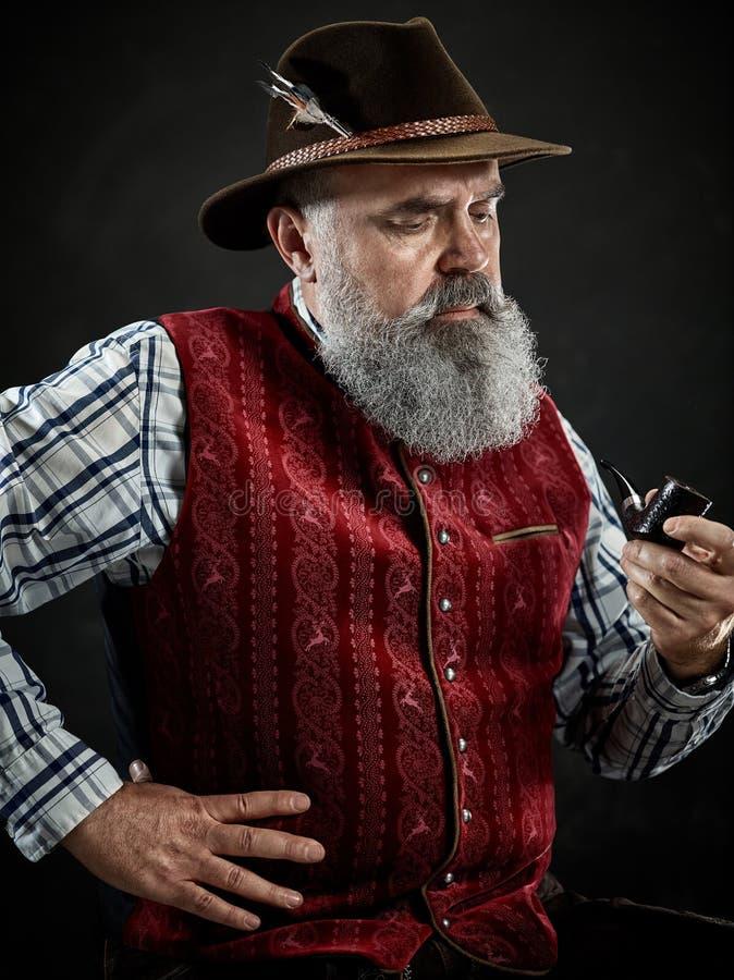 Dramatic portrait of senior smoking tobacco pipe. Dramatic portrait of gray bearded senior man in hat smoking tobacco pipe. view of Austrian, Tyrolean, Bavarian royalty free stock image