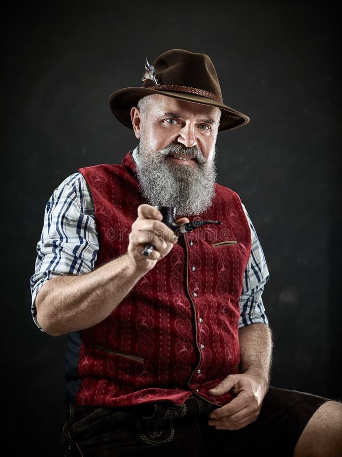 Dramatic portrait of senior smoking tobacco pipe. Dramatic portrait of gray bearded senior man in hat smoking tobacco pipe. view of Austrian, Tyrolean, Bavarian royalty free stock photos