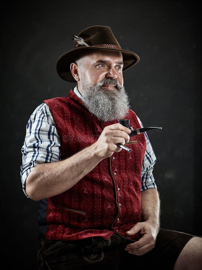 Dramatic portrait of senior smoking tobacco pipe. Dramatic portrait of gray bearded senior man in hat smoking tobacco pipe. view of Austrian, Tyrolean, Bavarian stock photos