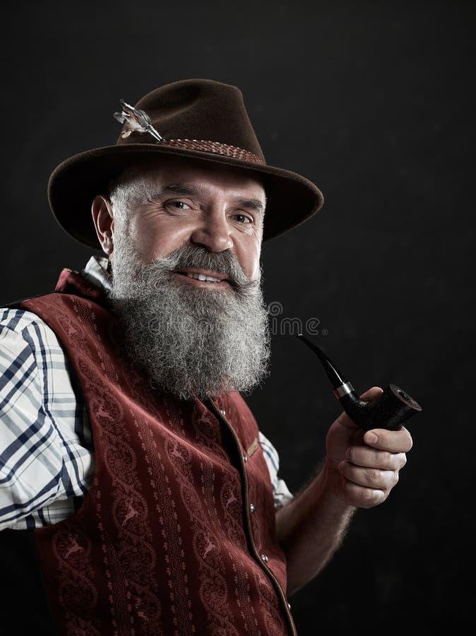 Dramatic portrait of senior smoking tobacco pipe. Dramatic portrait of gray bearded smiling senior man in hat smoking tobacco pipe. view of Austrian, Tyrolean royalty free stock photography