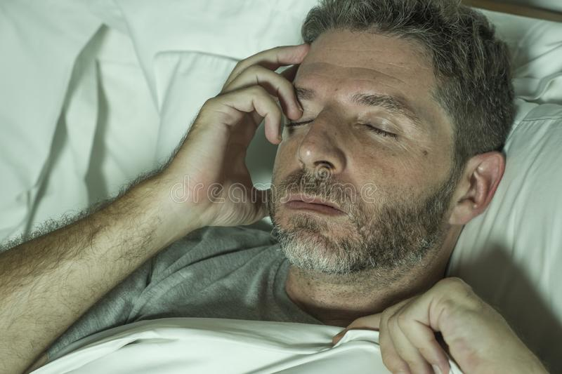 Dramatic portrait of stressed and frustrated man in bed awake at night suffering insomnia sleeping disorder tired and desperate royalty free stock photos
