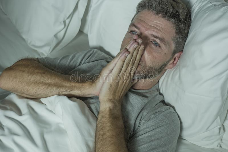 Dramatic portrait of stressed and frustrated man in bed awake at night suffering insomnia sleeping disorder tired and desperate stock photo