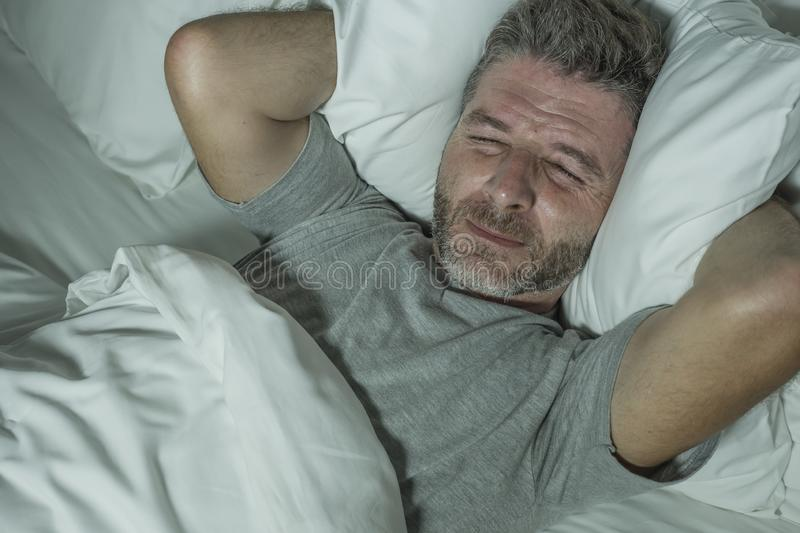Dramatic portrait of stressed and frustrated man in bed awake at night suffering insomnia sleeping disorder tired and desperate stock photos