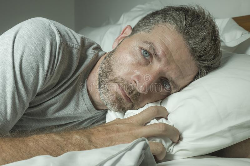 Dramatic portrait of stressed and frustrated man in bed awake at night suffering insomnia sleeping disorder tired and desperate royalty free stock image