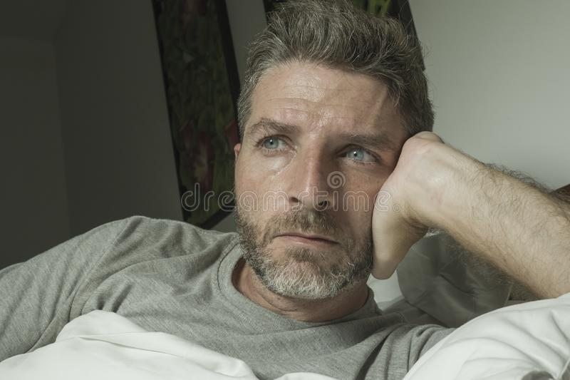 Dramatic portrait of stressed and frustrated man in bed awake at night suffering insomnia sleeping disorder tired and desperate stock photography