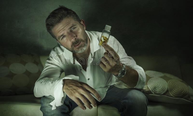 Dramatic portrait of young attractive depressed and wasted pills addict man holding antidepressant tablets bottle sitting on couch royalty free stock images