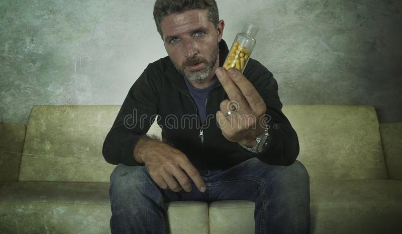 Dramatic portrait of young attractive depressed and wasted pills addict man holding antidepressant tablets bottle sitting on couch stock photos