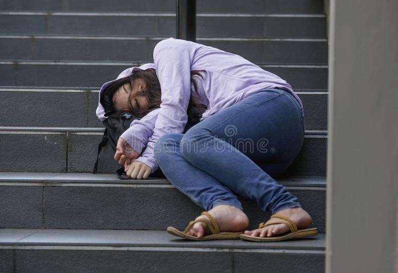 Oung depressed and intoxicated Asian student woman or teenager girl sitting on street staircase drunk or high on drugs suffering. Dramatic portrait of young royalty free stock photos