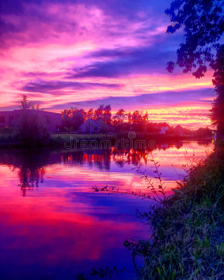 Dramatic purple sunset over the river. With the colors reflected in the water royalty free stock images