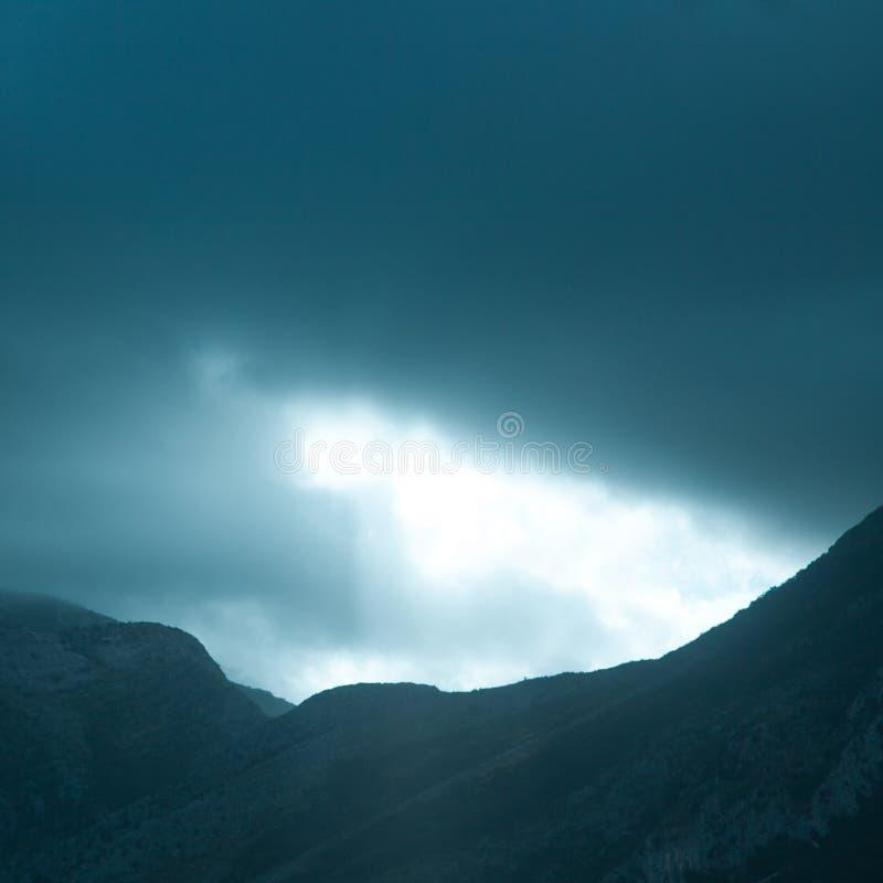 Dramatic rays of light pushing up through clouds. Square photo of dramatic rays of light pushing up through clouds stock image