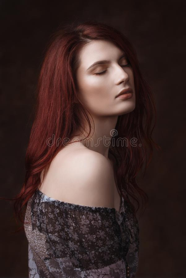 Dramatic retro portrait of a young beautiful dreamy redhead woman. Soft vintage toning. stock images