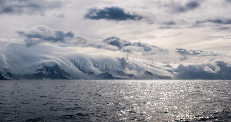 Dramatic rolling clouds, island off Antarctica. Dramatic rolling clouds over mountains on island off Antarctica royalty free stock photography