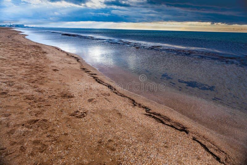 Dramatic scenery empty long sandy beach with cloudy storm sky. Dramatic scenery empty long sandy beach with shallow water and cloudy storm sky, Crimea, Ukraine royalty free stock photo