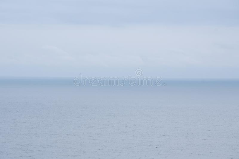 Dramatic seascape with grey cloudy sky over it. View of calm sea and grey cloudy sky stock photos