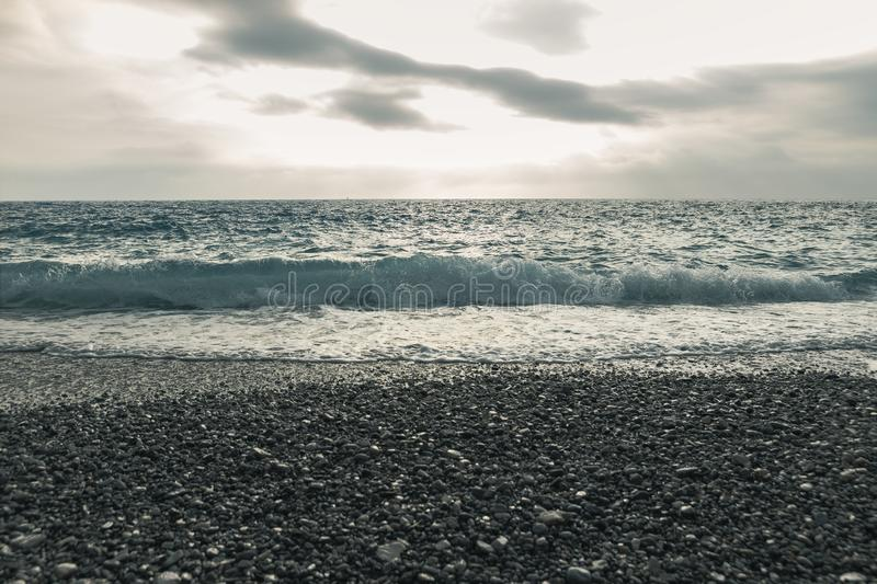 Dramatic seascape with waves in front of shingle beach.  royalty free stock images