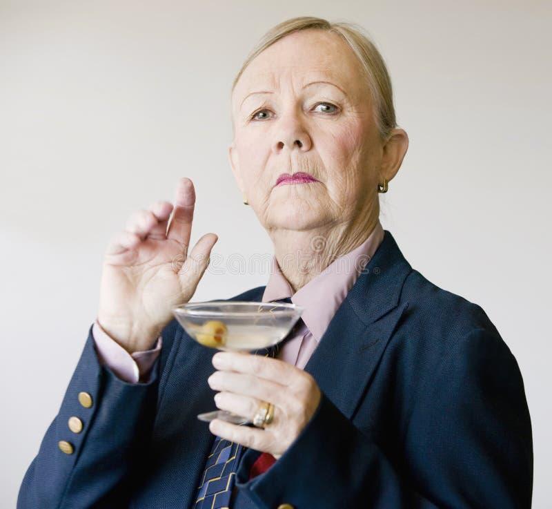 Dramatic Senior Woman with a Martini. Dramatic senior woman in a man's suit holding a Martini royalty free stock photos