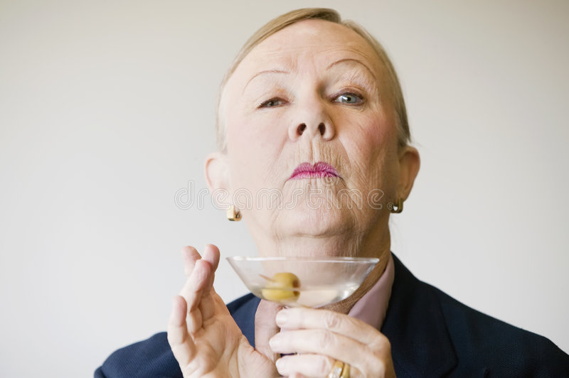 Dramatic Senior Woman with a Martini. Dramatic senior woman in a man's suit holding a Martini stock images