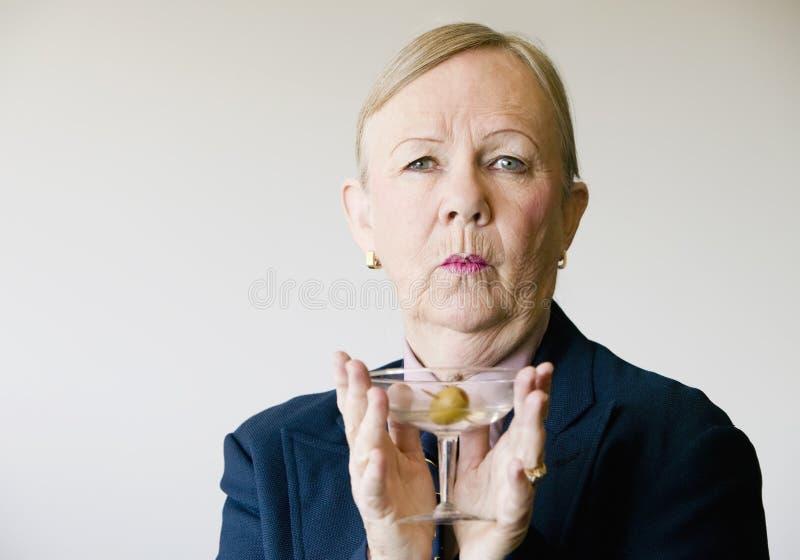 Dramatic Senior Woman with a Martini. Dramatic senior woman in a man's suit holding a Martini royalty free stock photo