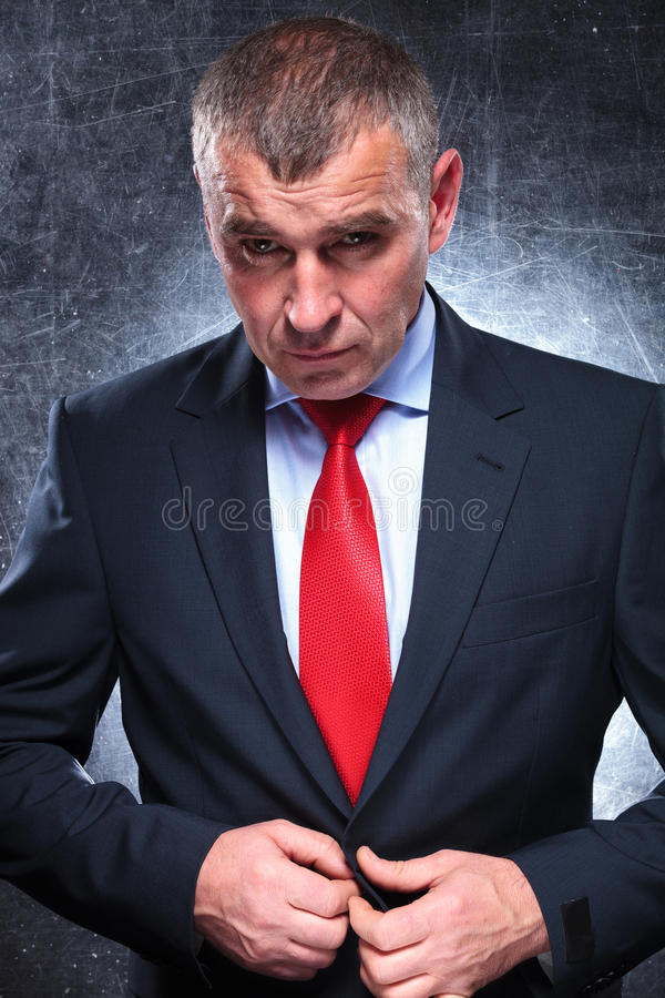 Dramatic serious mature business man unbuttoning his coat royalty free stock photos