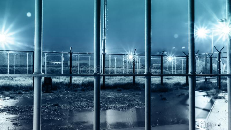Dramatic Shot Of High Security Prison Facility Yard From Inside Iron Bars During Rain Storm At Night royalty free stock image