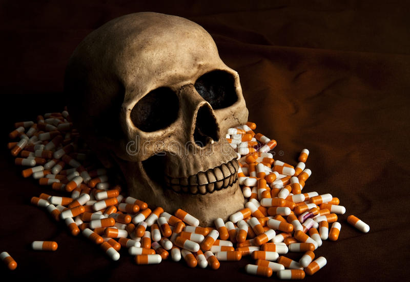 Dramatic sickness. Dramatic skull in the pile of drugs symbolises sickness and danger of abuse stock photos