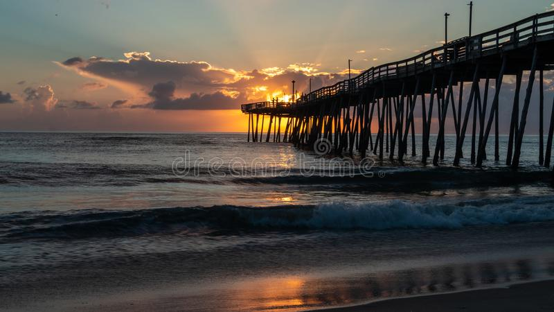 Dramatic sky lights up the clouds with an orange glow as fishermen cast their lines from the end of an old wooden pier at sunrise. royalty free stock images