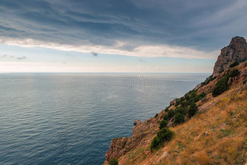 Dramatic sky, rocky coast and calm sea before stock images