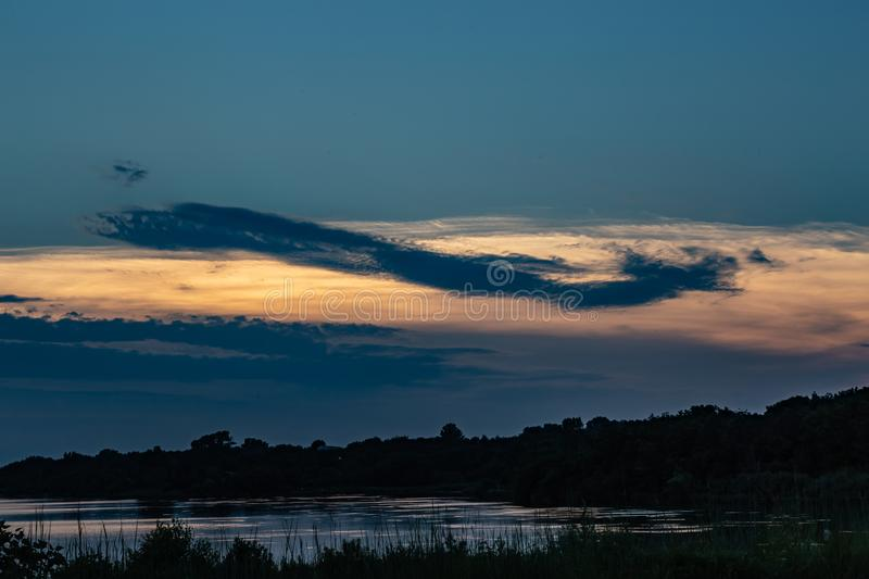 Is it a plane or a fish, Dramatic beautiful clouds at sunset over lake Zorinsky Omaha Nebraska. Dramatic skyline of the setting sun with beautiful clouds. Cloud stock photography
