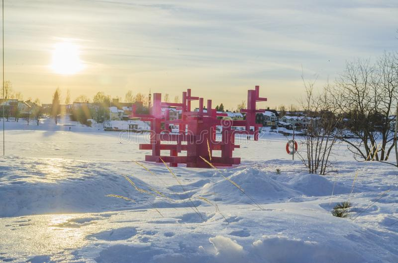 Dramatic snowscape in a frozen river with pink wooden architechture and house beyond the woods royalty free stock images