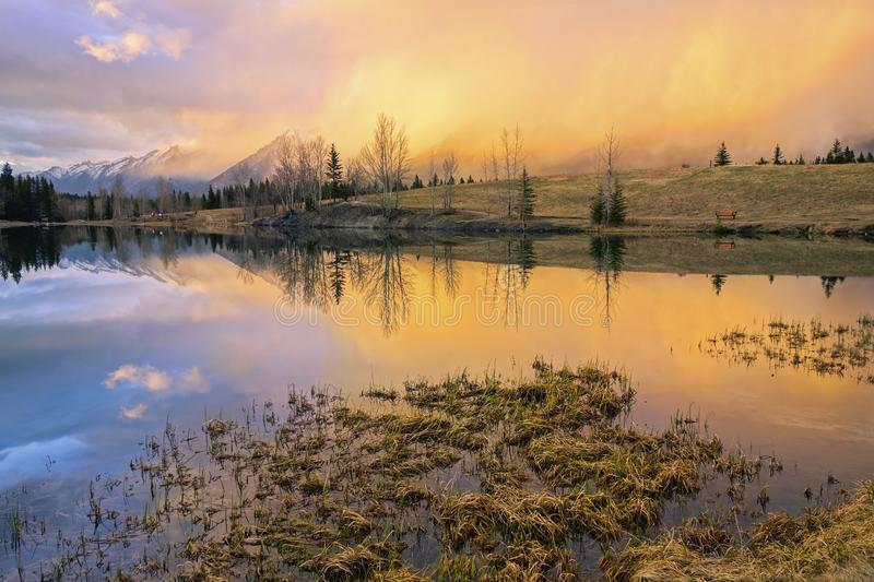 Dramatic Springtime Sunset Colors Blue Lake Canada Landscape Alberta Foothills. Springtime Mountain Landscape and Dramatic Sunset Colors at Quarry Lake above stock photo