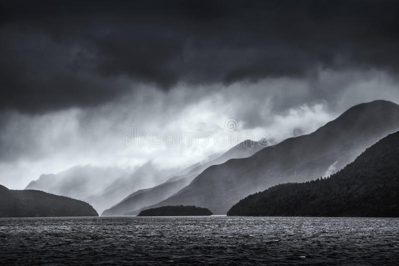 Dramatic storm clouds over receding layers of mountains over Doubtful Sound in New Zealand in monochrome. stock images