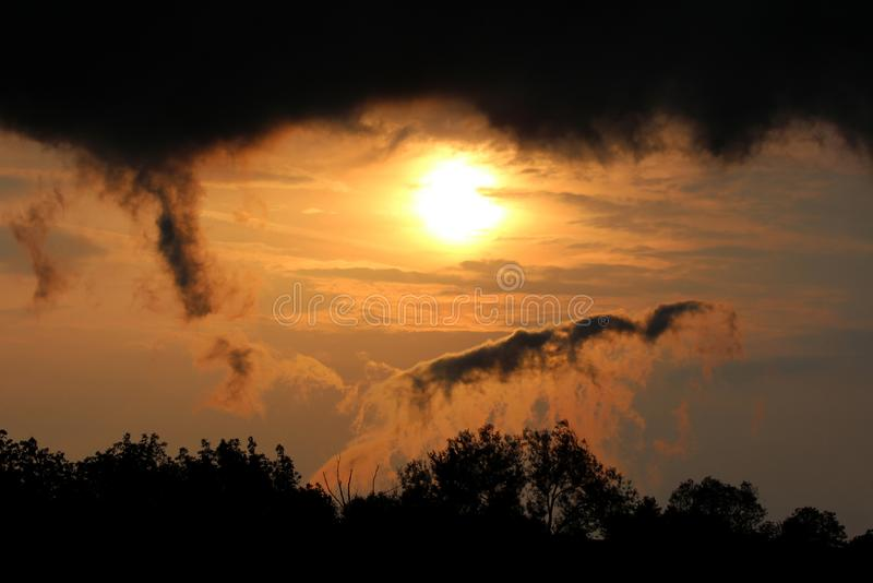 Dramatic stormy clouds surrounding sun at sunset over local forest. On warm sunny spring day stock images
