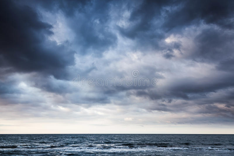 Dramatic stormy dark cloudy sky over sea. Natural photo background royalty free stock image