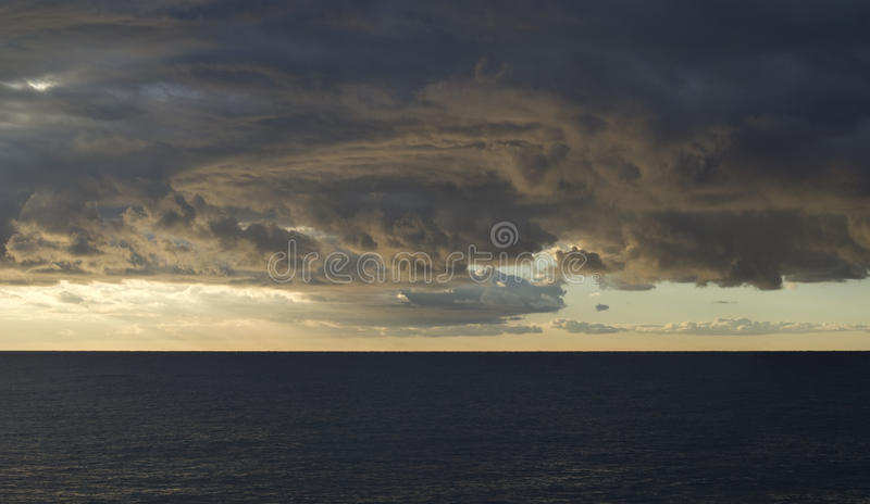 Dramatic stormy sky over sea. Dark cumulus clouds hovering over the sea royalty free stock image