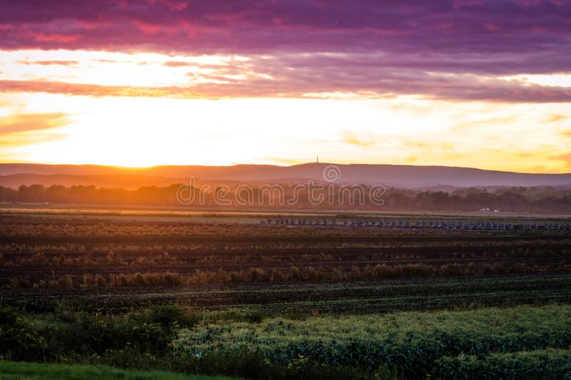 Summer sunset over farm valley during peak harvest royalty free stock photos
