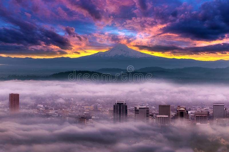 Dramatic Sunrise over Foggy Downtown Portland. Dramatic colorful sunrise over Mount Hood and foggy Portland Oregon city downtown royalty free stock image
