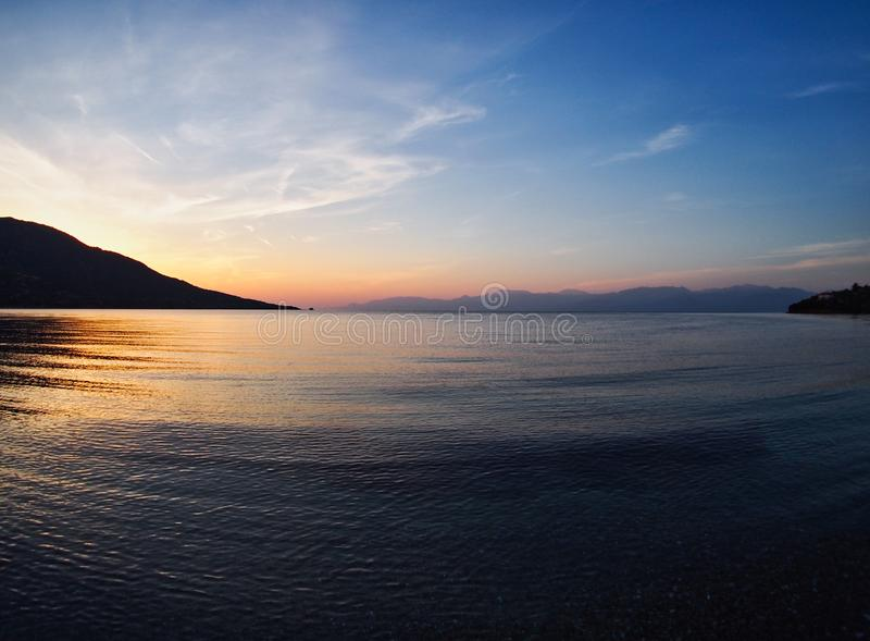 Dramatic Sunrise Over Gulf of Corinth, Greece. Dramatic dawn to sunrise transition over Corinthian Gulf bay, Ormos Lemonias, Greece, with contrast between lit stock photo