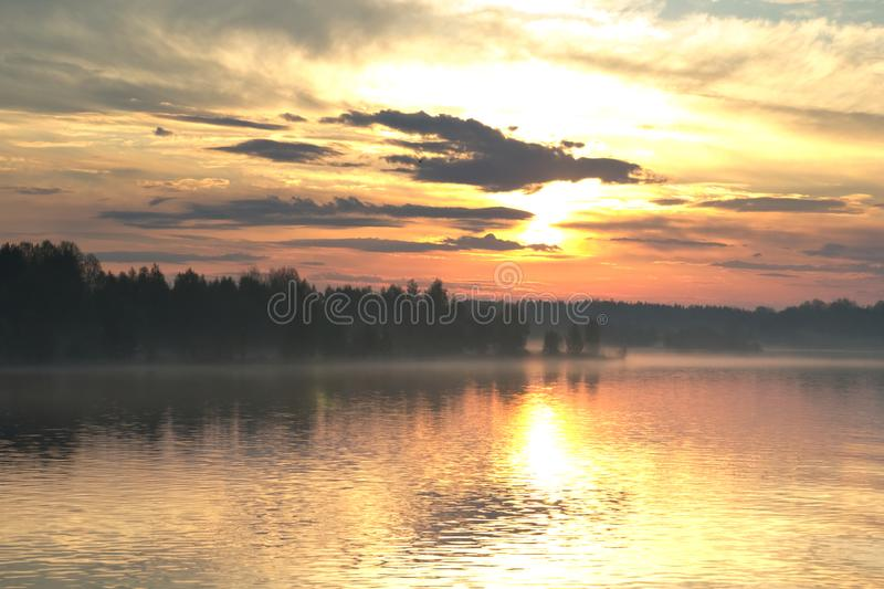 The dramatic sunrise over the river. The rays of the rising sun illuminate the clouds and mist over the river royalty free stock photography
