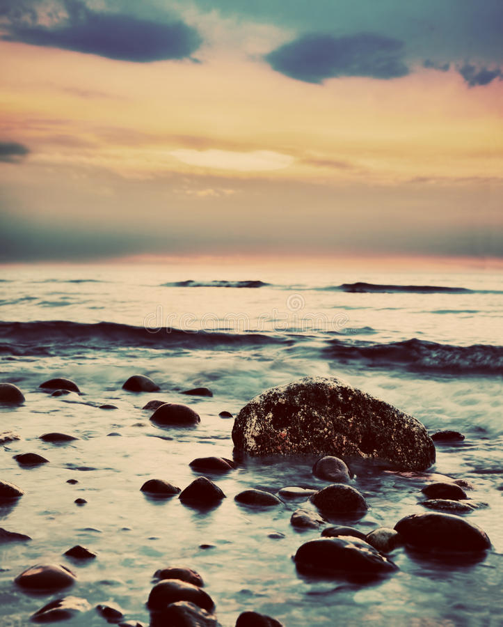Dramatic sunrise on a rocky beach. Retro, vintage royalty free stock photos