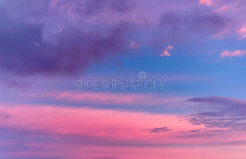 Dramatic sunset with clouds and pink orange blue sky royalty free stock image
