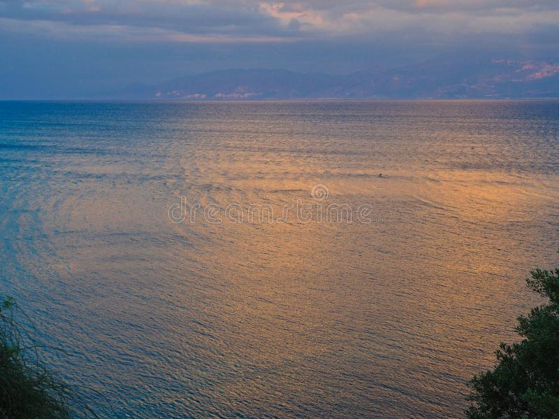 Dramatic Sunset Light on Clouds and Sea water, Greece. A dramatic Gulf of Corinth sunset, with orange to pink sunset-dusk light on clouds and reflected in the stock photography