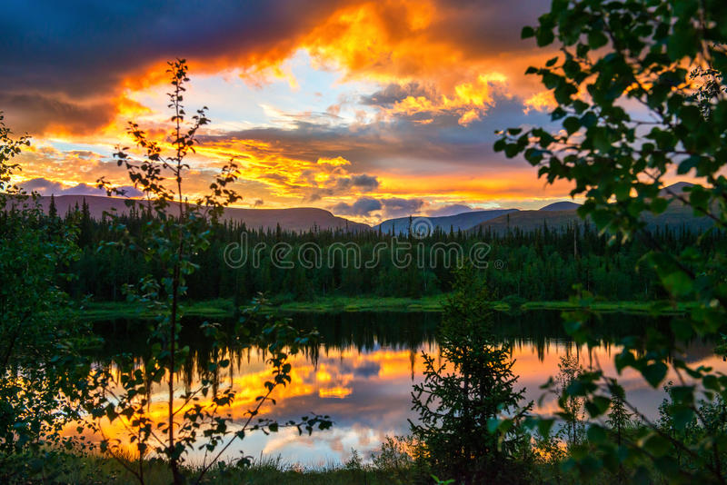 Dramatic sunset in the mountains. The light of the fading day, like a fire in the woods. Very beautiful light and reflection in a forest lake stock images