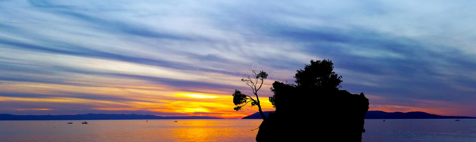 Dramatic sunset over the Adriatic Sea with Kamen Brela - Tiny famous island in Brela royalty free stock images