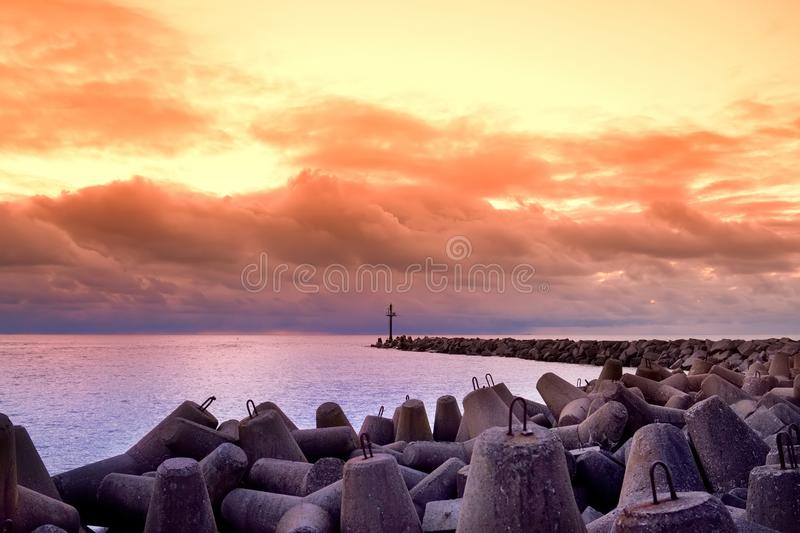 Dramatic sunset over the Baltic sea at winter. Purple clouds hovering over the waves on chilly winter day royalty free stock photography